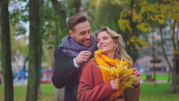 Happy romantic young couple with a man holding woman form behind standing in the golden autumn park enjoying the beautiful nature look straight ahead. High quality 4k resolution footage