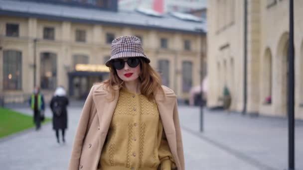 Posh smyslné luxusní mladá žena s hnědými vlasy v béžové podzimní kabát tanec venku s městským zázemím. Vysoce kvalitní záběry rozlišení 4k.