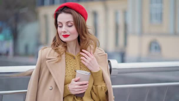 Charming young woman in red beret and stylish beige autumn coat touch her hair and smiles. Pretty French style lady standing outdoors urban city and holds coffee mug. 4K UHD