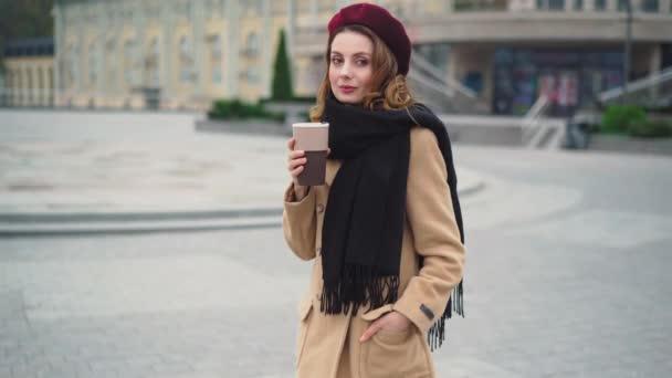 Poloviční portrét krásné dívky v červeném baretu a stylovém béžovém podzimním kabátě lehce tančící a usmívající se. Pretty francouzský styl dáma stojící venku městské město s hrnkem kávy. 4K UHD