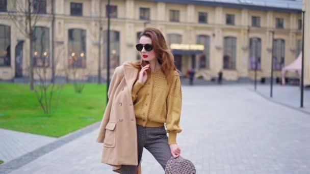 Posing Mode attraktive Frau mit einem Mantel hinter und Sonnenbrille auf im Freien. Professionelles Model posiert im trendigen Kleid vor urbanem Hintergrund. Mode, trendiges Konzept. 4K UHD