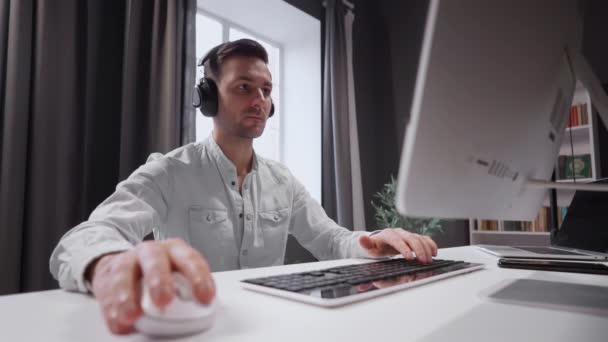 Young student is actively studying the subject remotely. Sits at the computer with headphones and works.