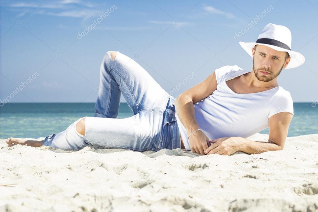 28a31bc7ad Homem na praia, deitado na areia, usando chapéu de verão hippie. Modelo  masculino
