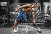 Svalnatý muž pracuje v tělocvičně dělá cvičení s činkami na triceps, silný muž nahý trup abs