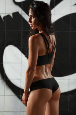 Sexy athletic woman from behind. Beautiful butt in thong. Fitness shaped girl