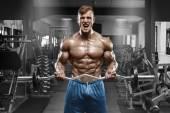 Svalnatý muž pracuje v tělocvičně dělá cvičení s činka na biceps, silný muž nahý trup abs