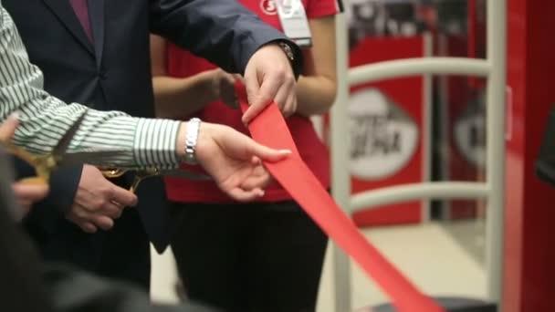 Otevření slavnostní červenou stužku nůžek v rukou