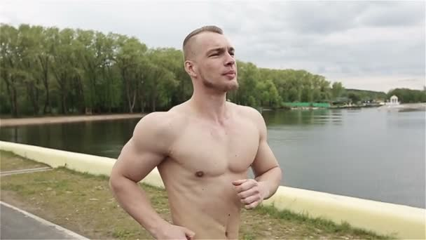 Muscular young man running outdoor. Slow motion