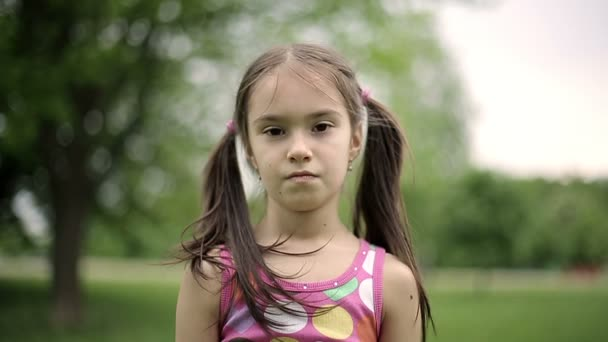 Portrait little girl is angry and disagrees crying in a summer park. Slow motion