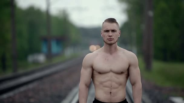 Muscular strong man stands on railroad tracks