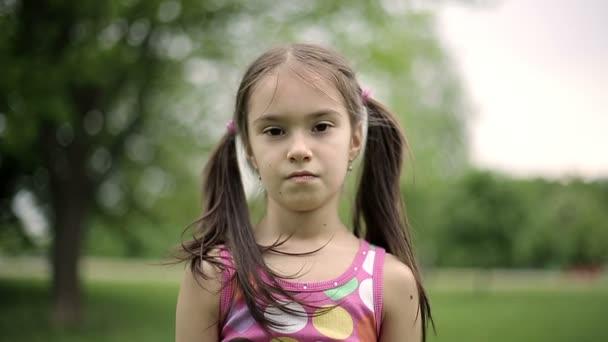 Ritratto bambina è arrabbiata e non è daccordo che grida in un parco di estate. Slow motion