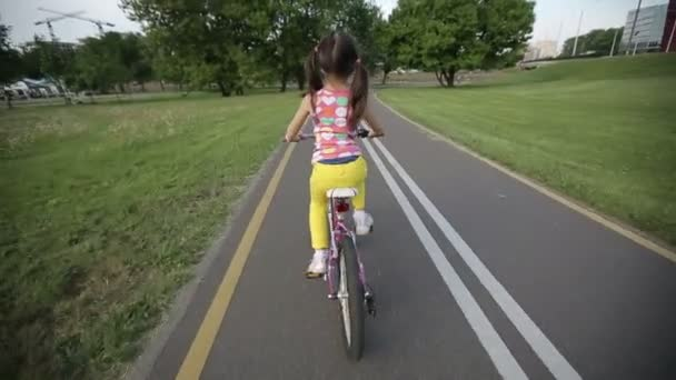 Little girl cycling in park on a pink bike