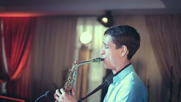 Saxophone player performs on stage with professional light.