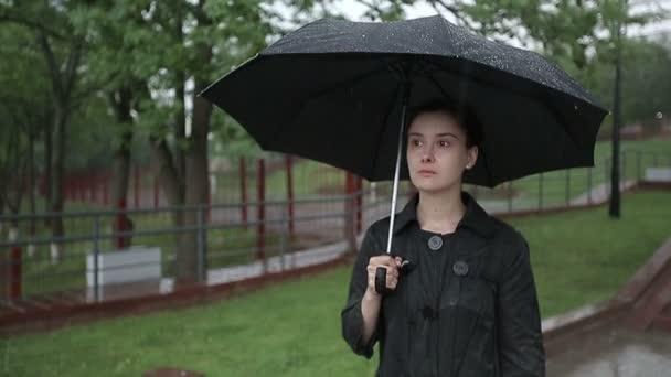 Osamělé dítě dívka v dešti s deštníkem. Zpomalený pohyb.