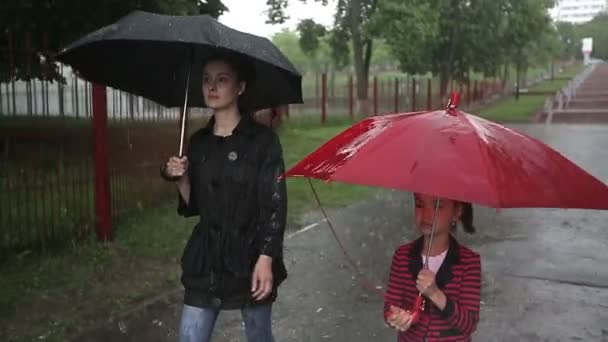 Mother and daughter walking on the street in heavy rain.