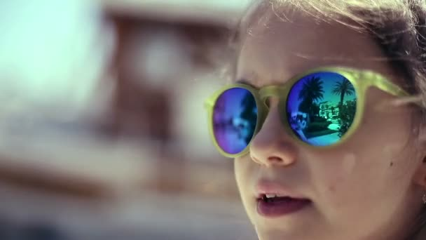 Child little girl on sea in sunglasses looking at palm. Palm trees are reflected
