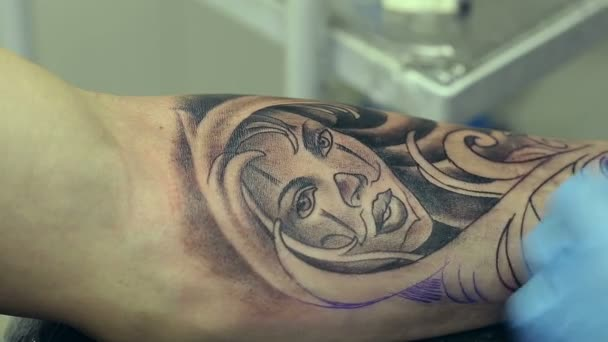 Tetovací umělec pracuje. Člověk čerpá z jeho ruku ženská tvář. Tattoo salón