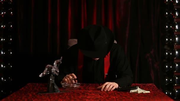 Gangster sedí u stolu s doutníkem a skryje tvář pod kloboukem