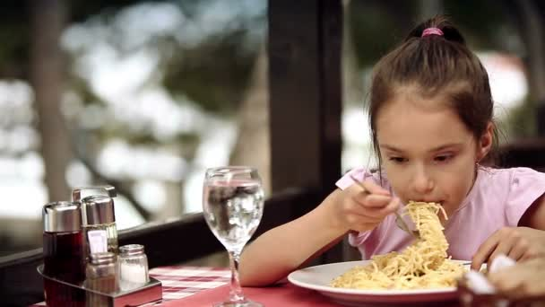 Child eats spaghetti pasta in the restaurant which is located on the shore of the Adriatic Sea.