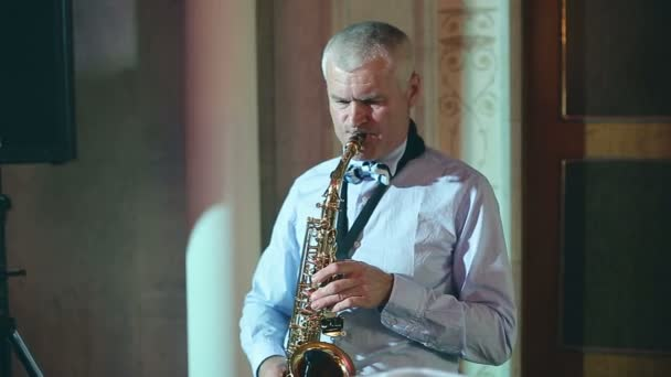 Middle-aged man saxophonist 50 years playing a musical instrument saxophone.