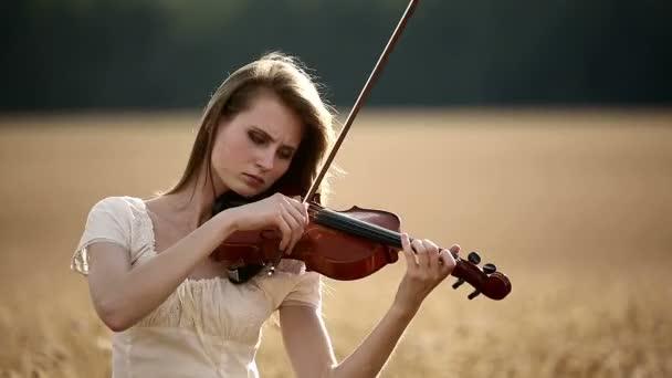 Geigerin spielt Geige im Weizenfeld.