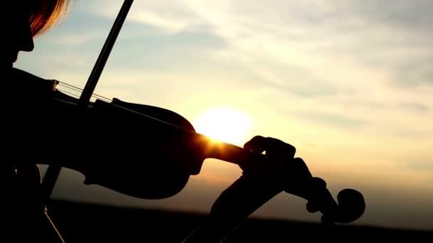 Sziluettjét lány hegedűművész hegedülni napnyugtakor ég háttér. Színes v.1