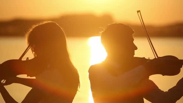 Hegedű Duett férfi és nő hegedülni a természet a naplementekor a tavon