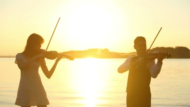 Violin duet man and woman play violin on nature at the sunset on the lake