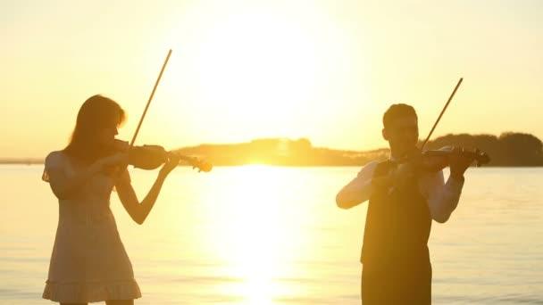 Violine-Duett-Mann und Frau spielen Violine auf Natur den Sonnenuntergang am See