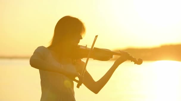 Female violinist playing the violin at the lake at sunset