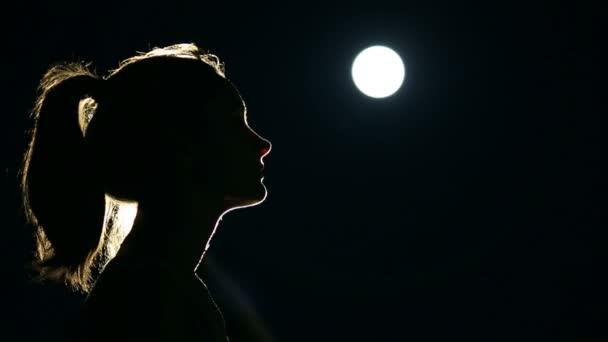 Silueta ženy, která se modlí v měsíčním světle