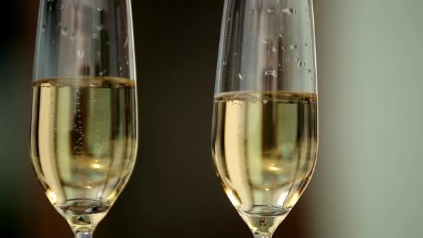Číšník drží tác dvou skleniček se šampaňským ukazuje návštěvníkům