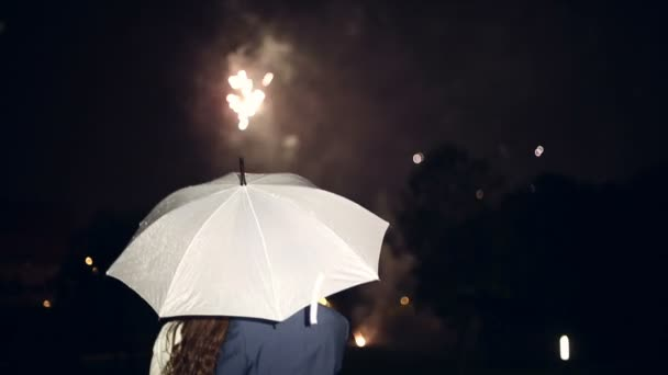 People stand under an umbrella and watch fireworks.