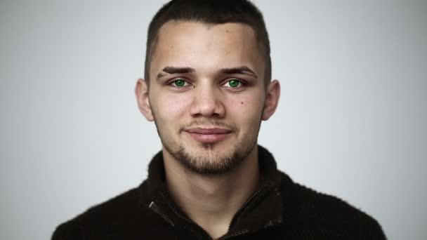 Mladý muž se zelenýma očima, usmíval se a ukazuje rovnátka na zuby