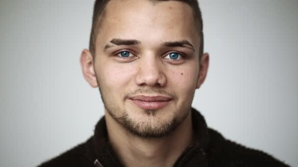 Mladý muž s modrýma očima, usmívala se a ukazuje rovnátka na zuby a mrkl