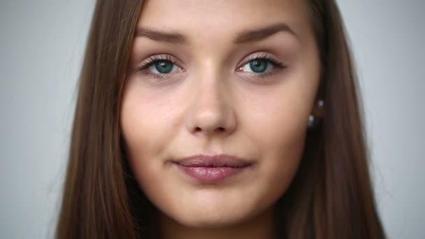 Zeitlupe: Junges Mädchen mit Klammern an den Zähnen, Blick in die Kamera und lächelnd