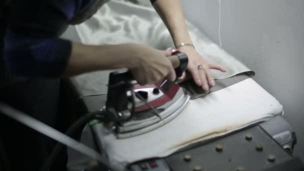Žena v oděvní továrně vyžehlila. Zblízka
