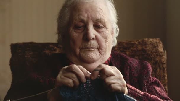 Stará žena sedí doma a plete oděvy