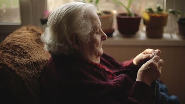 La vecchia donna si siede a casa e capi di maglieria