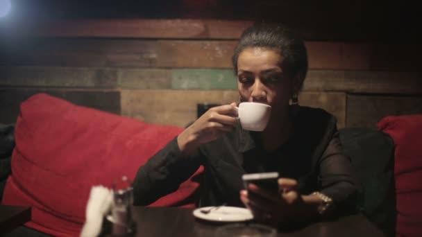 Černá žena pít horkou kávu a využít smartphone