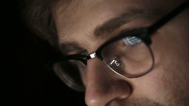 Portrét mladého muže s brýlemi, který pracuje v noci. Zblízka