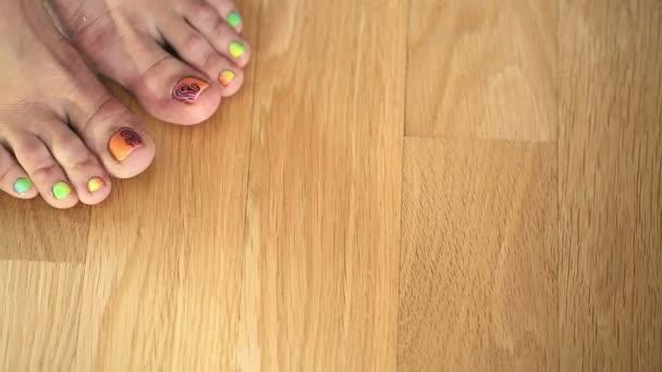 Ragazza in piedi sul pavimento di legno con una bella pedicure