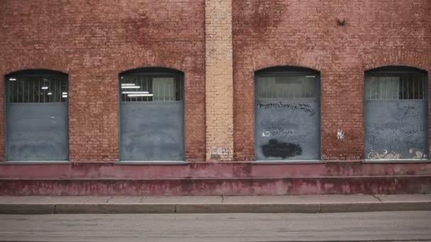 Úspěšný šťastný muž jde na pozadí cihlovou zeď staré továrny