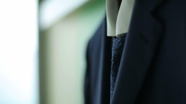 Pánský oblek visí na ramínku