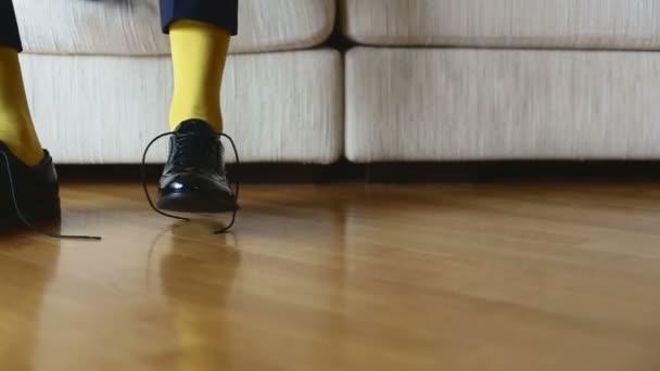 Muž v žluté ponožky nosí boty uvázat tkaničky
