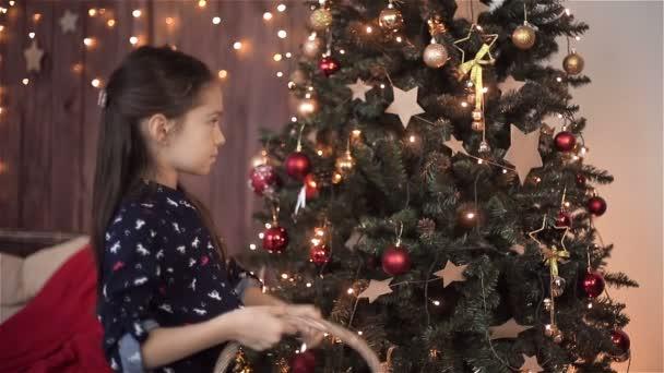 Kinder Mädchen schmückt den Weihnachtsbaum. HD-Aufnahme mit Schieberegler