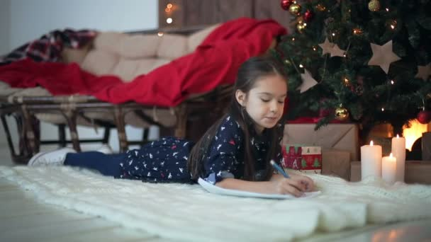Child girl writes a letter to Santa Claus. Dolly shot