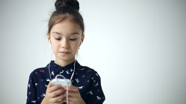 Child uses smartphone with earflaps at studio background