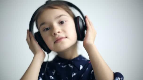 Dítě s sluchátka tančí na studio pozadí