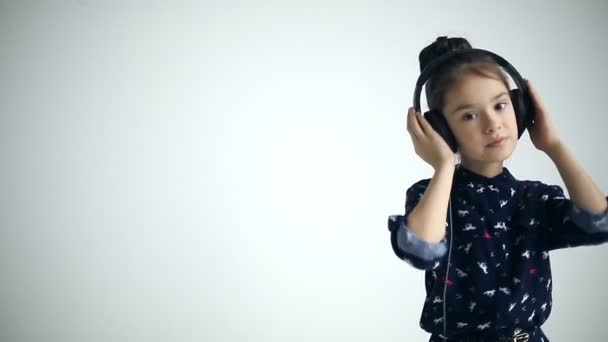 Child with headphones dancing at studio background